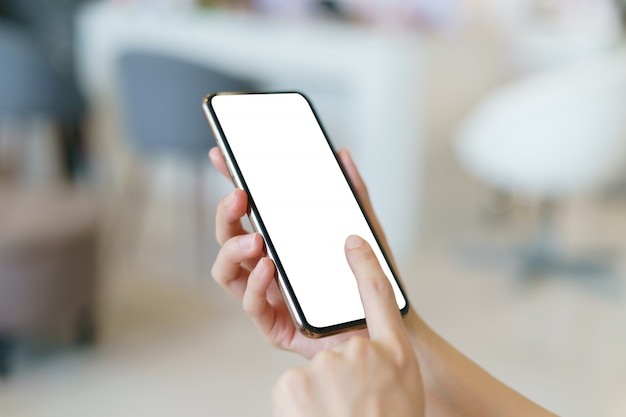 Mockup image of hand holding mobile phone with blank white screen.
