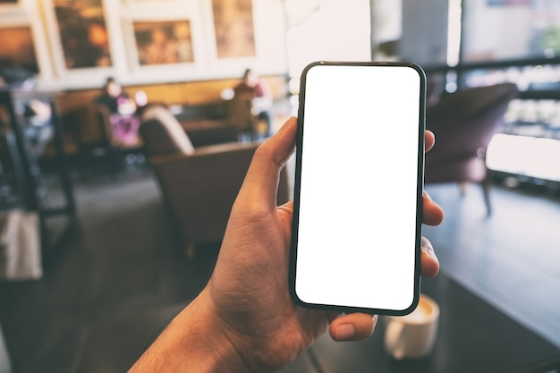 Mockup image of a hand holding and showing black mobile phone with blank white screen in cafe