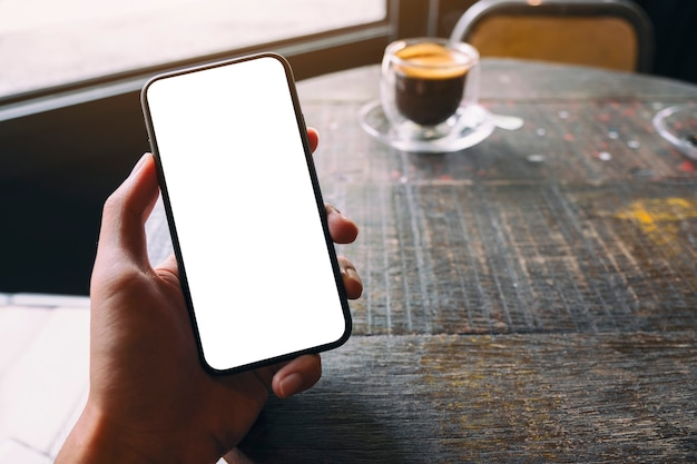 Mockup image of a hand holding and showing black mobile phone with blank white screen and coffee cup on wooden table