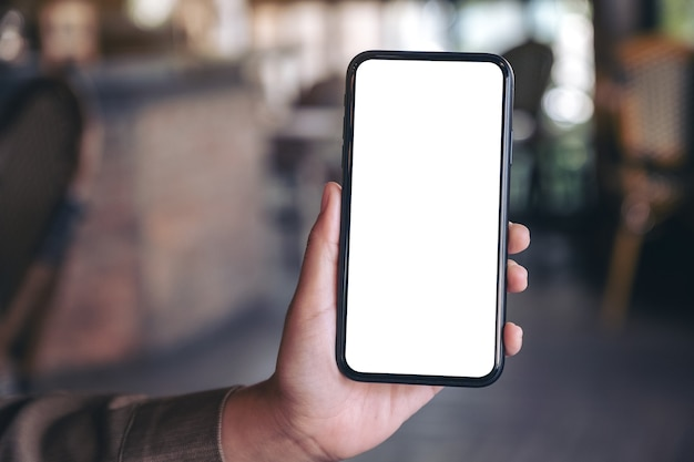 Mockup image of a hand holding and showing black mobile phone with blank white screen in modern cafe
