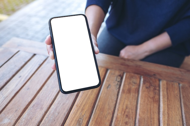 Mockup image of a hand holding and showing white mobile phone with blank black desktop screen to someone