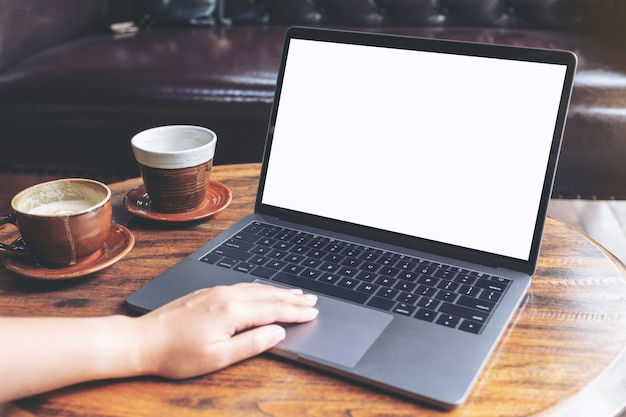 Mockup image of a hand using and typing on laptop with blank white screen and coffee cup on table in modern cafe