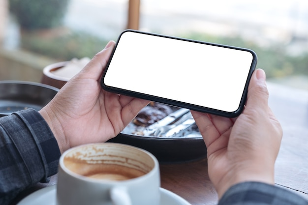 Mockup image of hands holding black mobile phone with blank desktop screen horizontally with coffee cup on the table