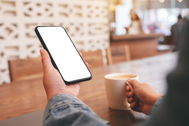 Mockup image of hands holding black mobile phone with blank desktop screen while drinking coffee in cafe
