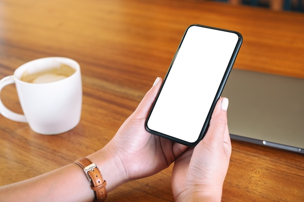 Mockup image of hands holding black mobile phone with blank desktop screen with laptop and coffee cup on the table