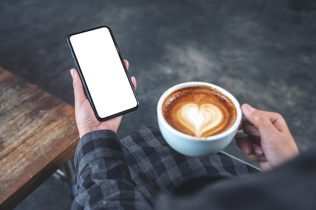 Mockup image of hands holding black mobile phone with blank screen while drinking coffee in cafe