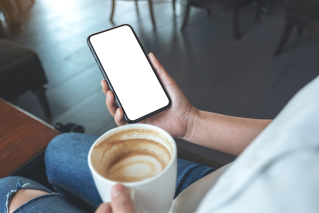 Mockup image of hands holding black mobile phone with blank screen while drinking coffee in modern cafe