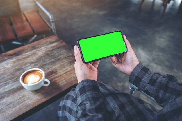 Mockup image of hands holding black mobile phone with blank white screen  horizontally with coffee cup on wooden table in vintage cafe
