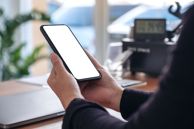 Mockup image of hands holding black mobile phone with blank white screen with laptop on wooden table in office