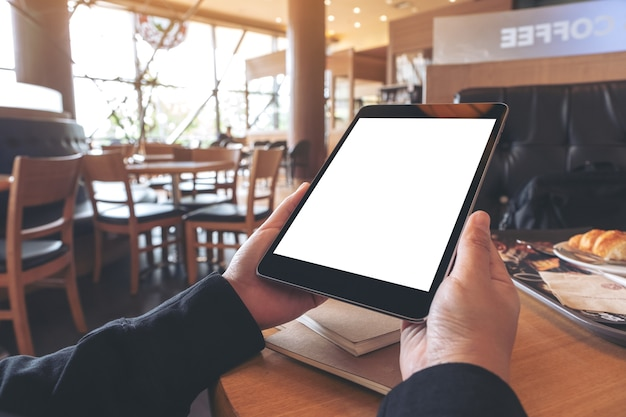 Mockup image of hands holding black tablet pc with blank screen with notebook and bread on wooden table in cafe
