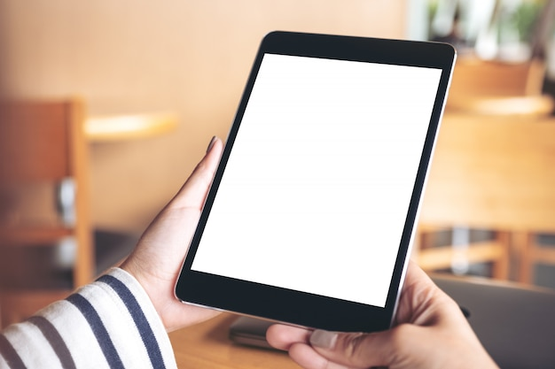 Mockup image of hands holding black tablet pc with blank white desktop screen on wooden table in cafe