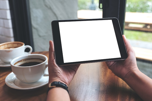 Mockup image of hands holding black tablet pc with white blank screen and coffee cups