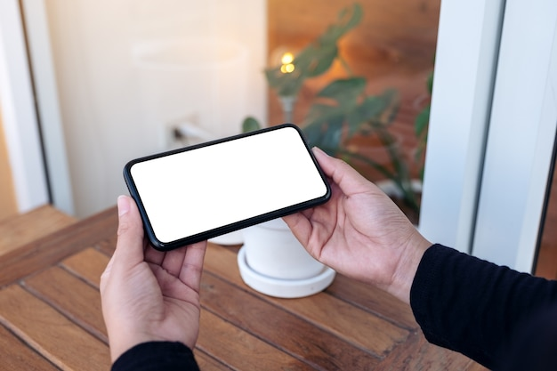 Mockup image of hands holding and using a black mobile phone with blank screen horizontally for watching in the outdoors