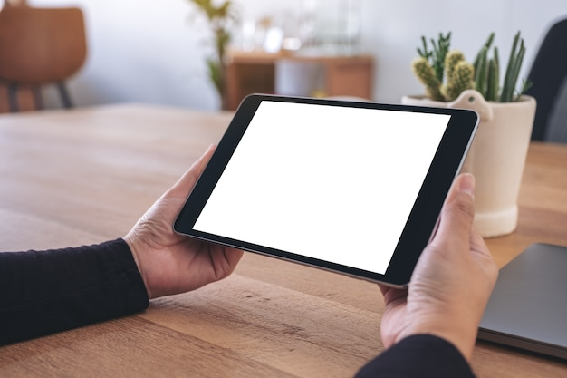 Mockup image of hands holding and using black tablet pc with blank white desktop screen with notebook on wooden table in office
