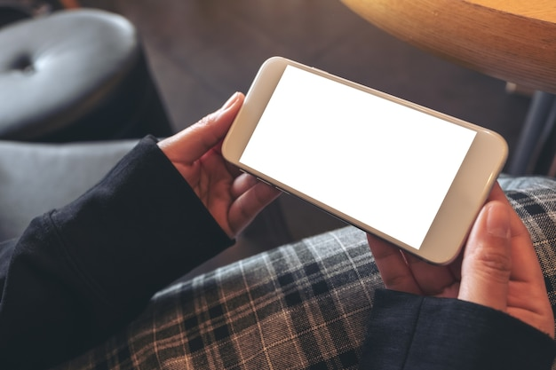 Mockup image of hands holding and using a white mobile phone with blank screen horizontally while sitting in cafe