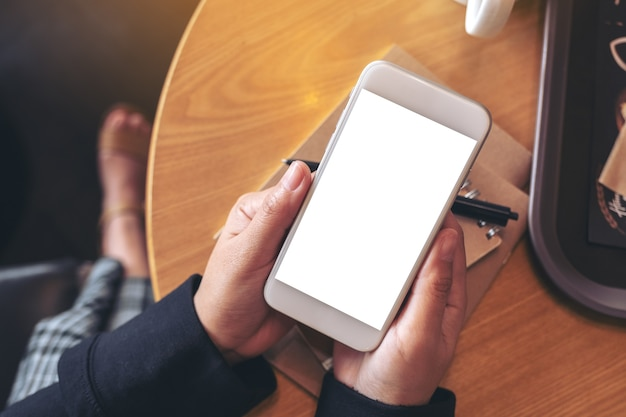 Mockup image of hands holding and using a white mobile phone with blank screen while sitting in cafe