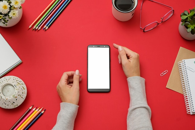 Mockup image of hands holding white mobile phone on red office desk.