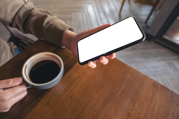 Mockup image of hands holding white mobile phone with blank screen while drinking coffee in cafe