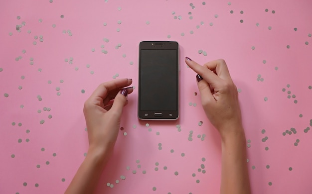 Mockup image of hands holding white mobile phone with modern pink office desk