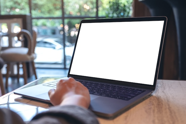 Mockup image of hands using and touching on laptop touchpad with blank white desktop screen