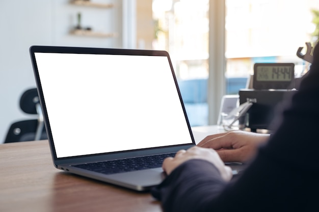 Mockup image of hands using and typing on laptop with blank white desktop screen on wooden table in office