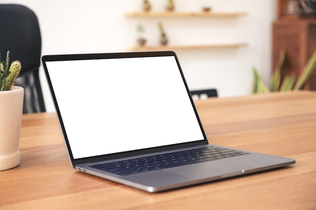 Mockup image of laptop with blank white desktop screen on wooden table