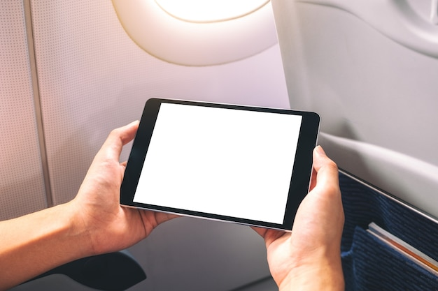 Mockup image of a man holding and looking at black tablet pc with blank white desktop screen next to an airplane window