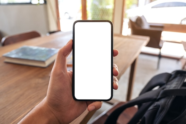 Mockup image of a man's hand holding black mobile phone with blank screen in cafe