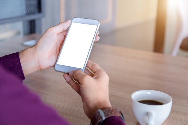 Mockup image of man's hands holding white mobile phone with blank screen technology.