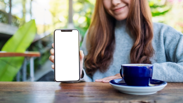 カフェで空白の画面で黒い携帯電話を保持し、表示している美しい女性のモックアップ画像