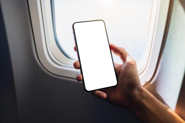 Макет изображения руки, держащей черный мобильный телефон с пустым экраном рабочего стола рядом с окном самолета