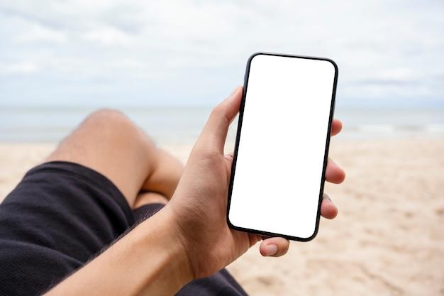 해변 의자에 앉아 있는 동안 빈 데스크탑 화면이 있는 검은색 휴대폰을 들고 보여주는 모형 이미지
