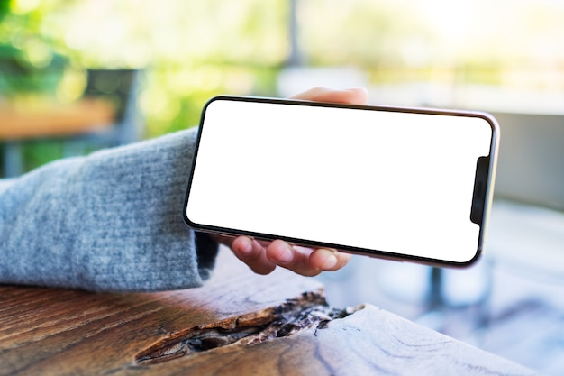 空白のデスクトップ画面で黒い携帯電話を持って表示している手のモックアップ画像