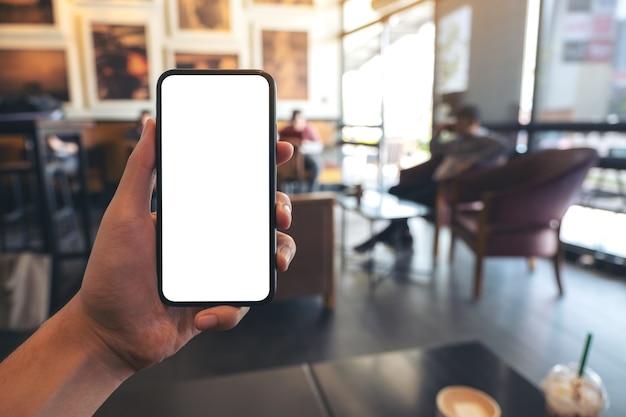 Изображение макета руки, держащей и показывающей черный мобильный телефон с пустым белым экраном в кафе