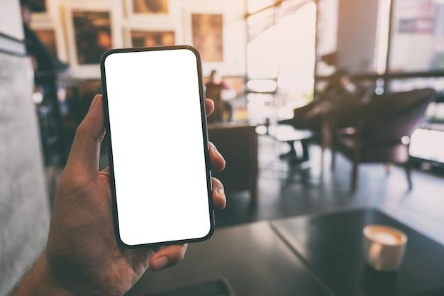 カフェで空白の白い画面と黒い携帯電話を持って見せている手のモックアップ画像