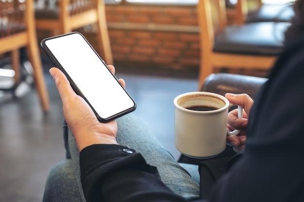 Макет изображения руки, держащей черный мобильный телефон с пустым экраном во время питья кофе в кафе