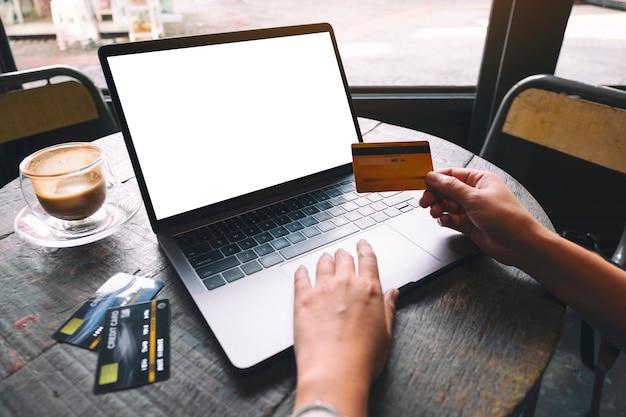 空白の白い画面と木製のテーブルの上のコーヒーカップでラップトップを使用して入力しながらクレジットカードを持っている手のモックアップ画像