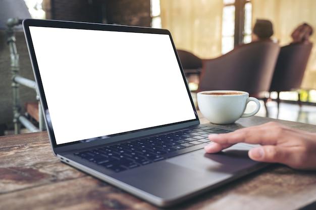 空白の白いデスクトップ画面でノートパソコンのタッチパッドを使用して触れている手のモックアップ画像