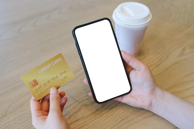 Изображение модель-макета рук держа кредитную карточку и черный мобильный телефон на кафе.