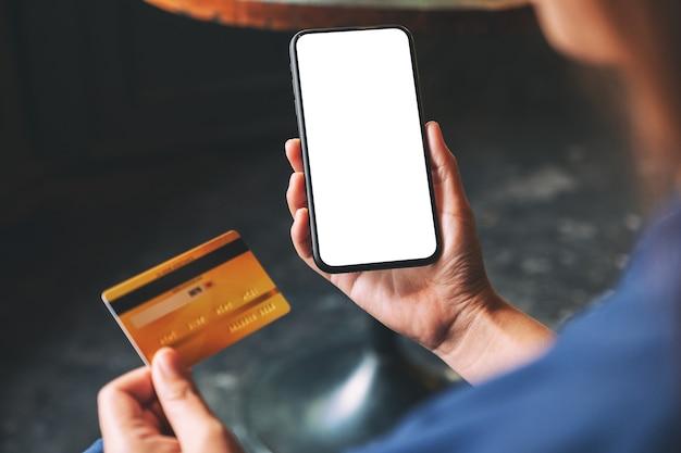 신용 카드를 들고 있는 손과 빈 데스크탑 화면이 있는 검은색 휴대폰의 흉내낸 이미지