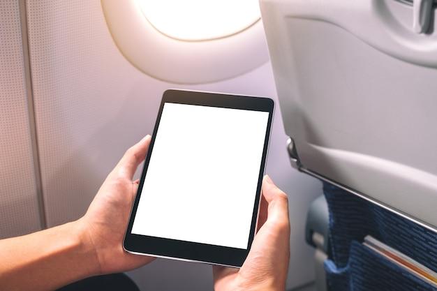 비행기 창 옆에 빈 흰색 바탕 화면이있는 검은 태블릿 pc를 들고보고있는 남자의 모형 이미지