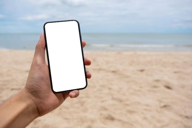 해변에 서 있는 동안 빈 데스크탑 화면이 있는 검은색 휴대폰을 들고 있는 남자의 모형 이미지