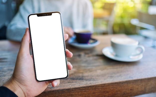 カフェでコーヒーを飲む女性と空白の白い画面で黒い携帯電話を保持している男性のモックアップ画像