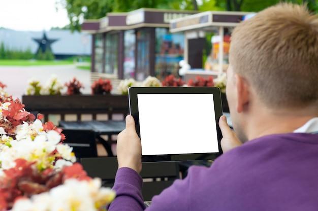 Макет изображения человека, держащего в руке черный планшет с пустым белым экраном