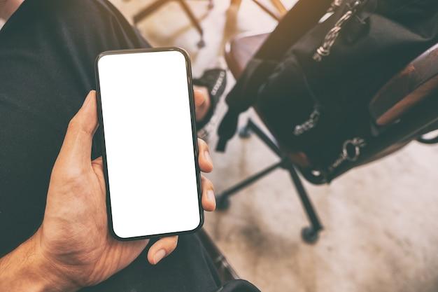 カフェのテーブルの上に一杯のコーヒーと空白の画面で黒い携帯電話を持っている男の手のモックアップ画像