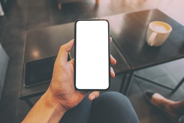 Мокап изображения мужской руки, держащей черный мобильный телефон с пустым экраном с чашкой кофе на столе в кафе