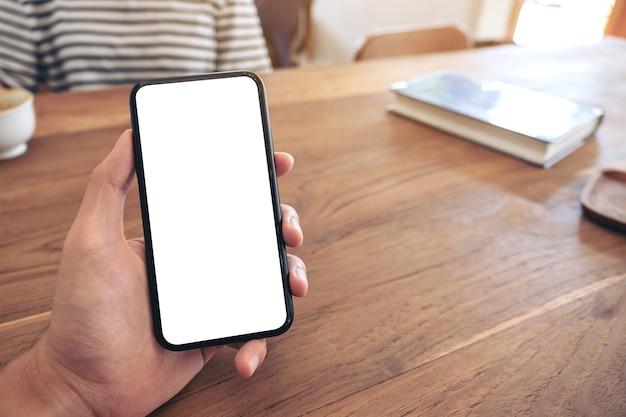 カフェで女性と空白の画面で黒い携帯電話を持っている男の手のモックアップ画像