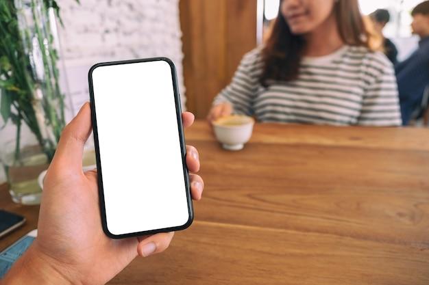 Мокап изображения мужской руки, держащей черный мобильный телефон с пустым белым экраном с женщиной, сидящей в кафе