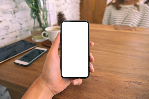 カフェに座っている女性と空白の白い画面で黒い携帯電話を持っている男の手のモックアップ画像