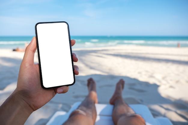 ビーチチェアに横になっている間空白のデスクトップ画面で白い携帯電話を持っている男の手のモックアップ画像